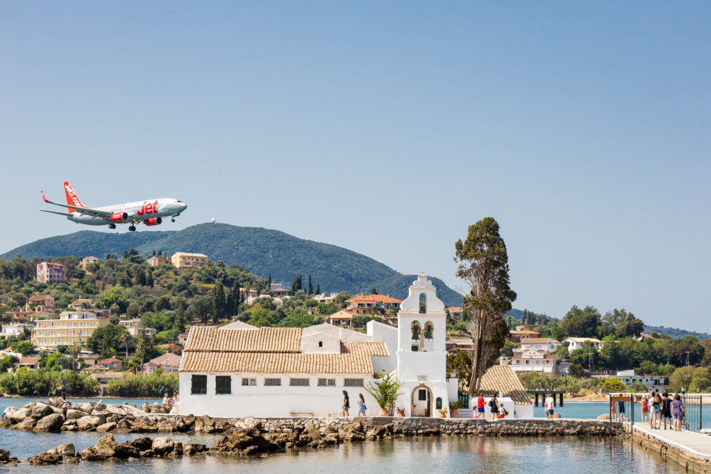 Corfu Greece Travel Guide: airplane flying over Vlacherna Monastery