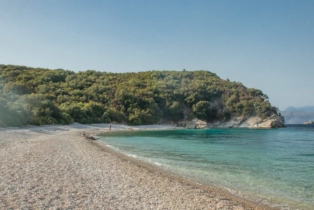 the best things to do in Corfu: secluded akoli beach with greenery and blue water